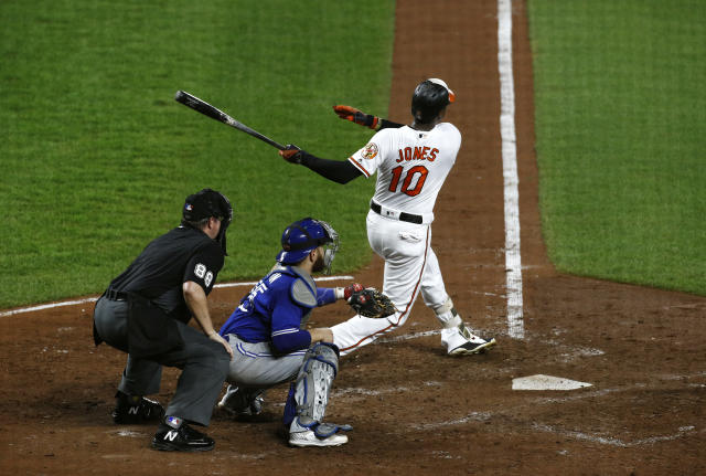 Baltimore Orioles' Adam Jones (10) watches his grand slam in front of Toronto Blue Jays catcher Russell Martin and umpire Doug Eddings in the fifth inning of a baseball game, Wednesday, Aug. 29, 2018, in Baltimore. (AP Photo/Patrick Semansky)