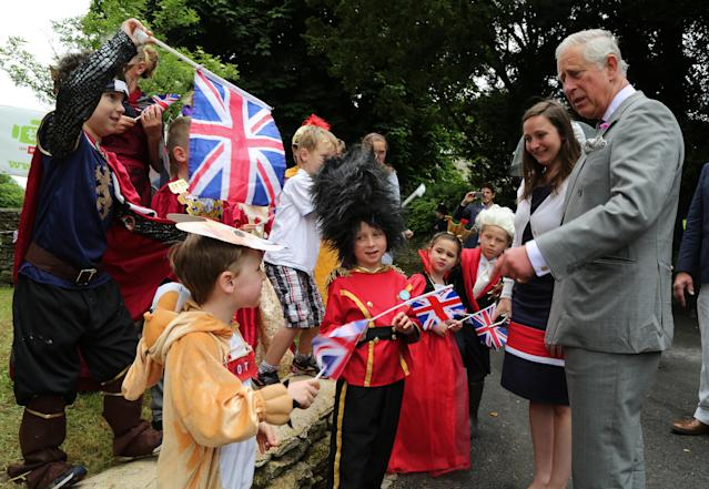 <p>Prince Charles, Prince of Wales, meets 3-year-old Monty Shepherd (second from left), who is dressed as a corgi, and other children in costume, as he attends a street party. (Photo by Geoff Caddick — WPA Pool/Getty Images) </p>