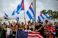 People in Miami wave Cuban and American flags as they demonstrate in support of the protests in Havana, on July 12, 2021