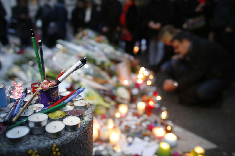 People light candles outside the offices of the French satirical newspaper Charlie Hebdo in Paris on January 10, 2015 (AFP Photo/Thomas Samson )