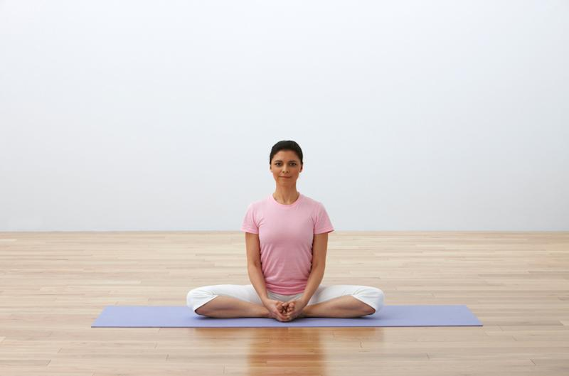 "This pose helps to open the hips and ease sciatica discomfort that can be made worse by sitting for long periods. Sit up tall with the soles of the feet touching and knees spreading open, bringing the feet in toward the pelvis and clasping your hands around your feet. Flap the knees up and down several times like butterfly wings, then sit still and focus the weight of the hips and thighs into the floor, easing pain in the sciatic nerve. ""The sciatic nerve starts in the lower back and runs down both leg, and sciatic nerve pain can occur when the nerve is somehow compressed,"" Bielkus says. ""Long commutes and sitting for long periods of time exacerbates it."""