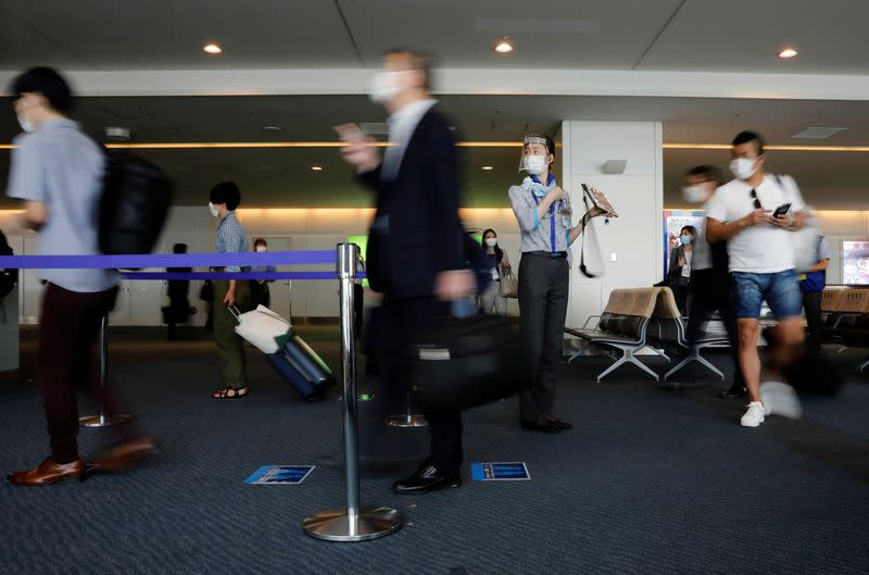 A staff member of All Nippon Airways wearing a protective mask and a face shield works at a boarding gate amid the coronavirus disease (COVID-19) outbreak at Haneda airport in Tokyo
