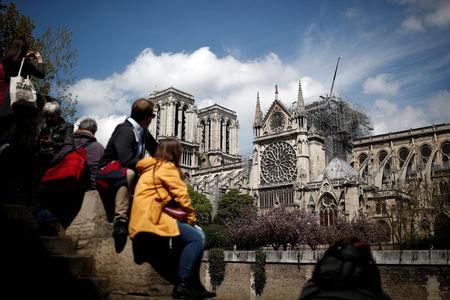 People look at Notre-Dame Cathedral two days after a massive fire devastated large parts of the gothic structure in Paris