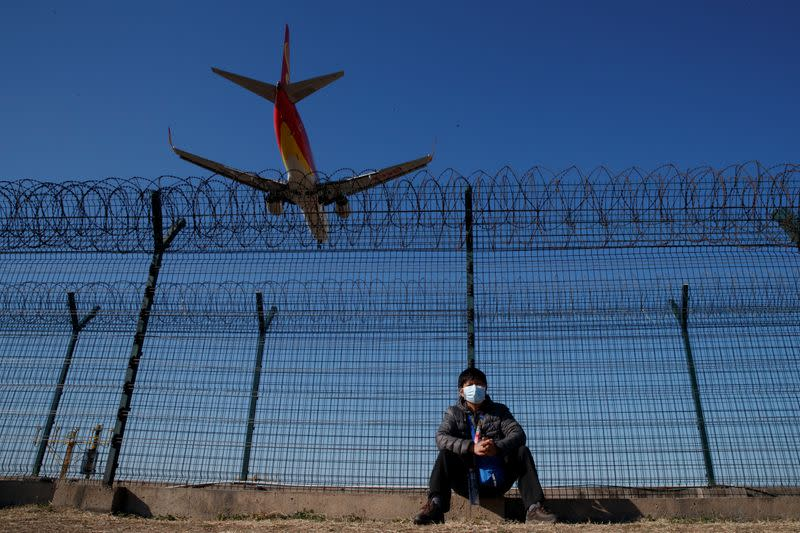A man wearing a protective mask sits at a fence surrounding Beijing Capital International as a plane lands in Beijing as the country is hit by an outbreak of the novel coronavirus