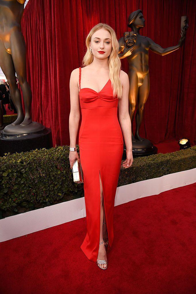 <p>The actor matched her vampy-red lip to her Louis Vuitton slip gown featuring mismatched straps in 2017.</p>