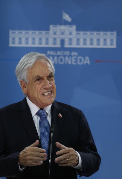 """Chilean President Sebastián Piñera addresses the nation from La Moneda presidential palace, amid ongoing demonstrations triggered by an increase in subway fares in Santiago, Chile, Monday, Oct. 21, 2019. Protesters defied an emergency decree and confronted police in Chile's capital Monday, continuing violent clashes, arson and looting that have left at least 11 dead and led the president to say the country is """"at war."""" (AP Photo/Luis Hidalgo)"""
