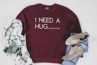<p>This <span>I Need A Hug E Glass Of Wine Sweater</span> ($30, originally $33) will make them laugh.</p>