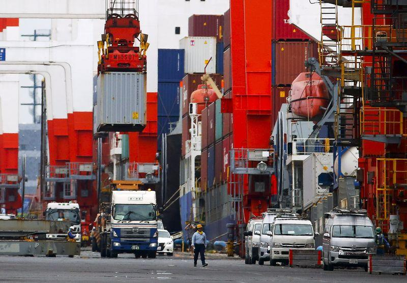 Crane lifts cargo container onto a truck at port in Tokyo