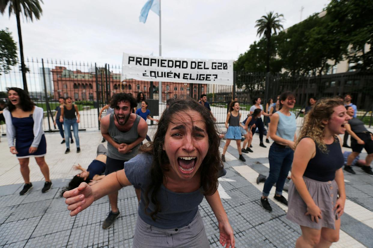 """Demonstrators perform outside the presidential palace ahead of the Group 20 summit, in Buenos Aires, Argentina, on Thursday. The writing on the banner reads: """"Property of the G20, who chooses?"""" (Photo: Sergio Moraes/Reuters)"""