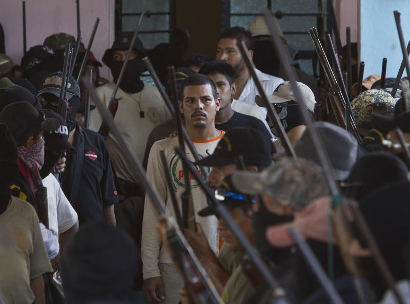 Masked members of the community of Ayutla escort detained people to a community assembly in the town of El Meson, Mexico, Thursday Jan. 31, 2013. Vigilantes who have taken up arms against drug cartel violence and common crime in southern Mexico brought charges ranging from organized crime to kidnapping and extortion against 50 men and three women who they have been holding prisoner at improvised jails, in some cases for weeks. (AP Photo/Christian Palma)