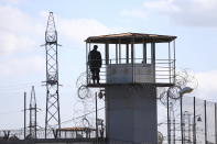 A soldier stands guard on a prison's watchtower as Georgian opposition supporters of former president Mikheil Saakashvili gather for a rally in his support in front of the prison where former president is being held, in Rustavi, about 20 km from the capital Tbilisi, Georgia, Monday, Oct. 4, 2021. Saakashvili was detained in Tbilisi on Saturday, Oct. 1, 2021. Georgia earlier declared Saakashvili wanted as a person convicted in absentia in several criminal cases and treated as a suspect in some others. Georgian authorities have warned repeatedly that he would be detained immediately once over the border. (AP Photo/Zurab Tsertsvadze)