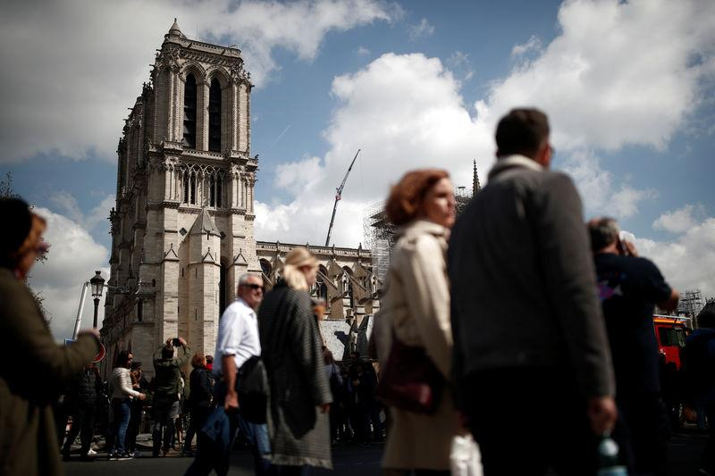 People walk past Notre-Dame Cathedral two days after a massive fire devastated large parts of the gothic structure in Paris