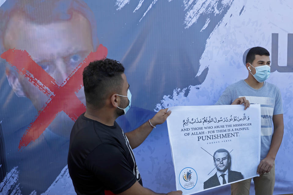 Hamas supporters hold a poster with a defaced picture of French President Emmanuel Macron during a protest against the publishing of caricatures of the Prophet Muhammad they deem blasphemous, in front of the French Cultural center in Gaza City, Tuesday, Oct. 27, 2020. (AP Photo/Adel Hana)