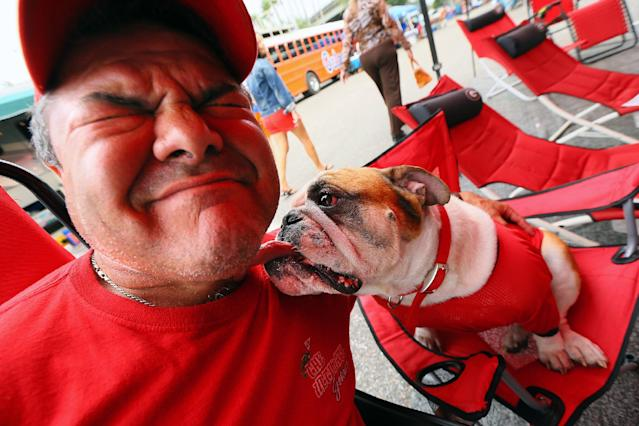 Preston McCallum, of Macon, gets a lick from his Bulldog named Dooley while tailgating next to EverBank Field on Friday, Nov. 1, 2013, in Jacksonville, Fla. The Georgia Bulldogs play the Florida Gators on Saturday in an NCAA football game. (AP Photo/Atlanta Journal-Constitution, Curtis Compton)