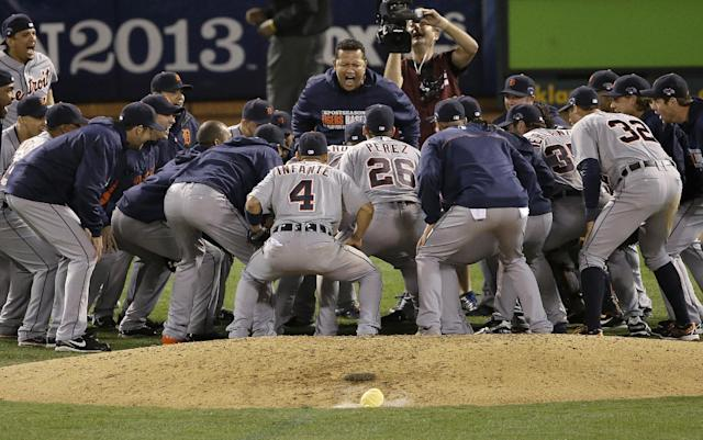 Detroit Tigers third baseman Miguel Cabrera, center top, celebrates with teammates after they defeated the Oakland Athletics in Game 5 of an American League baseball division series in Oakland, Calif., Thursday, Oct. 10, 2013. The Tigers won 3-0. (AP Photo/Jeff Chiu)
