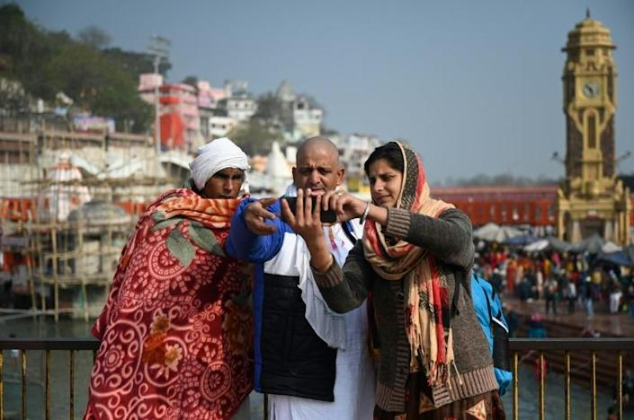 A family takes selfies on the banks of the Ganges