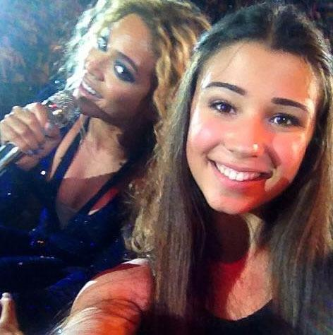 Selfie of girl with Beyoncé in the background
