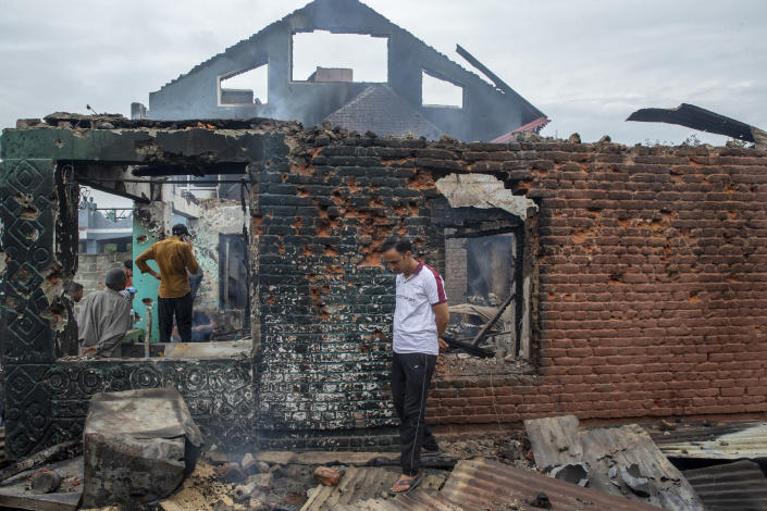 Kashmiri villagers inspect a house destroyed in a gunfight in Pulwama, south of Srinagar, Indian controlled Kashmir, Wednesday, July 14, 2021. Three suspected rebels were killed in a gunfight in Indian-controlled Kashmir on Wednesday, officials said, as violence in the disputed region increased in recent weeks. Two residential houses were also destroyed. (AP Photo/ Dar Yasin)