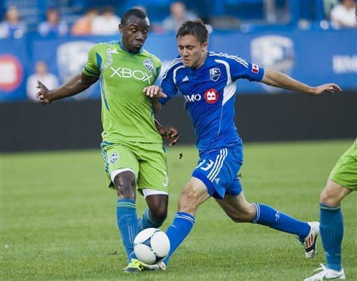 Montreal Impact's Andrew Wenger, right, tackles Seattle Sounders' Jhon Kennedy Hurtabo during the first half of an MLS soccer game in Montreal, Saturday, June 16, 2012. (AP Photo/The Canadian Press, Graham Hughes)