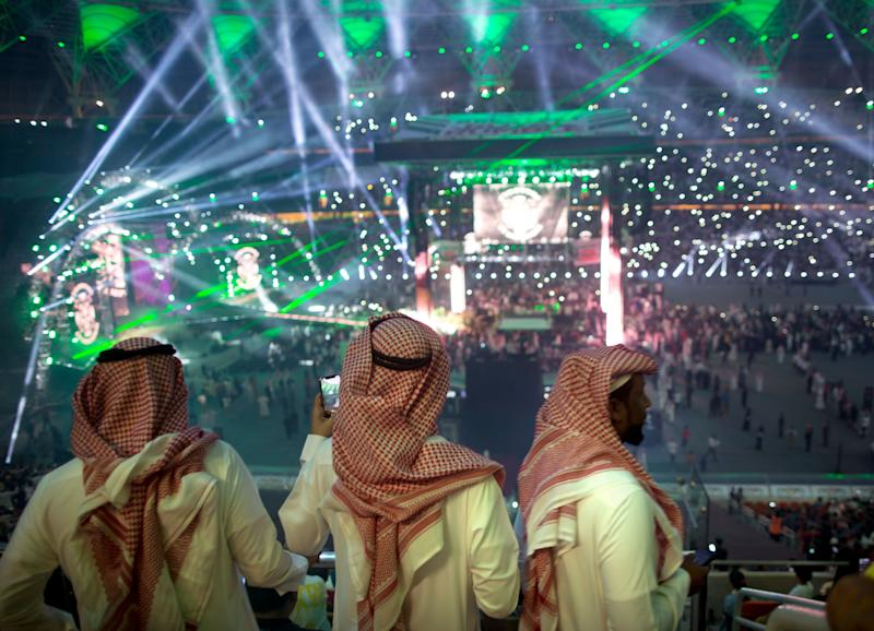 """Fans film the opening of the """"Greatest Royal Rumble"""" event in Jiddah, Saudi Arabia, Friday, April 27, 2018. A previous WWE event held in the ultraconservative kingdom in 2014 was for men only. But Friday night's event in Jiddah included both women and children in attendance. (AP Photo/Amr Nabil)"""