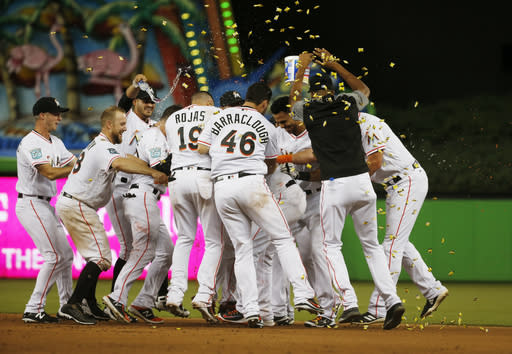 Miami Marlins' Starlin Castro is mobbed by teammates after he hit a walk-off single in the 12th inning of a baseball game against the Milwaukee Brewers on Wednesday, July 11, 2018, in Miami. The Marlins won 5-4. (AP Photo/Wilfredo Lee)