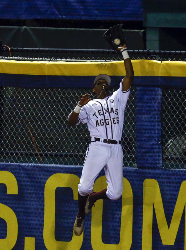 Texas A&M outfielder Allonte Wingate robs Auburn's Conor Davis of a home run as he catches the ball at the fence during the third inning of a Southeastern Conference tournament NCAA college baseball game, Thursday, May 24, 2018, in Hoover, Ala. (AP Photo/Butch Dill)