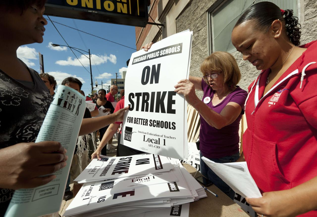 FILE - In this Saturday, Sept. 8, 2012 file photo, members of the Chicago Teachers Union distribute strike signage at the Chicago Teachers Union strike headquarters in Chicago. The Chicago Teachers Union announced Sunday night that its 25,000 members will go on strike Monday morning, Sept. 10, 2012, for the first time in 25 years after contract talks with the school district failed over issues that included benefits and job security. (AP Photo/Sitthixay Ditthavong)