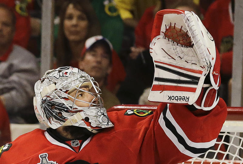 Chicago Blackhawks goalie Corey Crawford (50) gloves the puck on a shot attempt by the Boston Bruins in the third period during Game 2 of the NHL hockey Stanley Cup Finals, Saturday, June 15, 2013, in Chicago. (AP Photo/Nam Y. Huh)