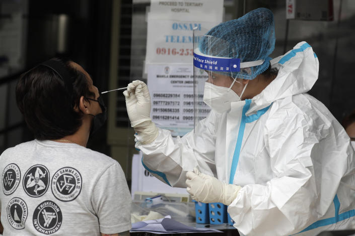 A health worker performs a COVID-19 test on a man at a hospital in Manila, Philippines on Monday, April 26, 2021. COVID-19 infections in the Philippines surged past 1 million Monday in the latest grim milestone as officials assessed whether to extend a monthlong lockdown in Manila and outlying provinces amid a deadly spike or relax it to fight recession, joblessness and hunger. (AP Photo/Aaron Favila)