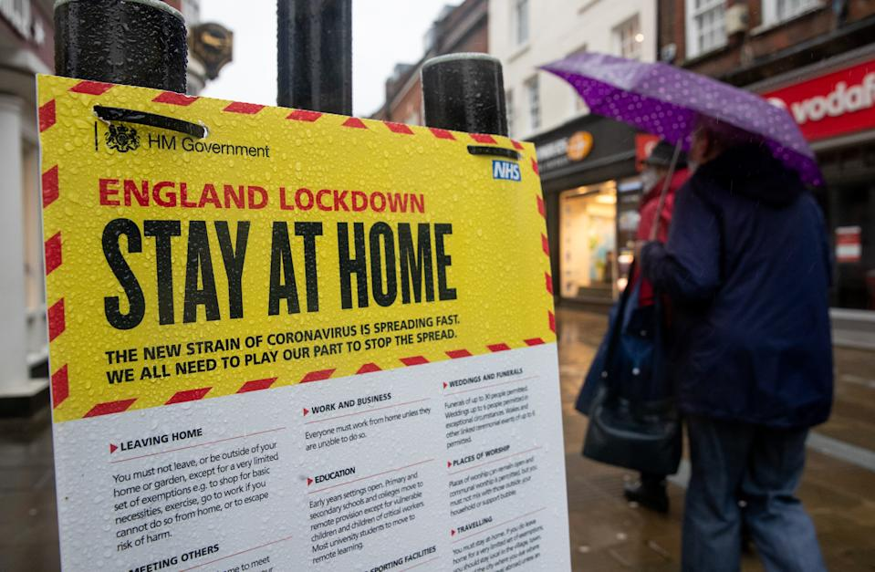 People walk past a Government sign warning people to stay at home on the High street in Winchester, Hampshire, during England's third national lockdown to curb the spread of coronavirus. Picture date: Wednesday January 20, 2021. (Photo by Andrew Matthews/PA Images via Getty Images)