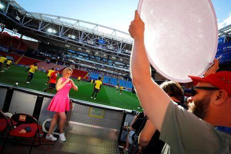 A TV presenter gets ready for her live-take during a training session of Colombia at the Spartak stadium in Moscow, Russia, July 2, 2018. REUTERS/Kai Pfaffenbach