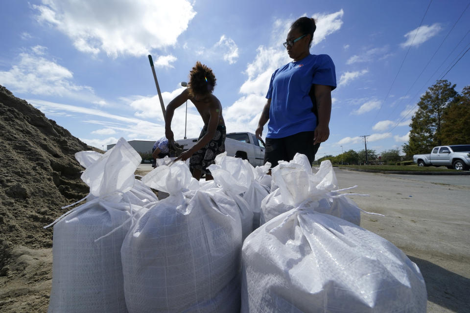 Stephanie Verrett and Jodie Jones fill sandbags to protect their home in anticipation of Hurricane Delta, expected to arrive along the Gulf Coast later this week, in Houma, La., Wednesday, Oct. 7, 2020. (AP Photo/Gerald Herbert)
