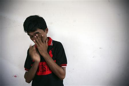 Bozor Mohammed from the Rakhine state in Myanmar stands near a wall after an interview at his house in Kuala Lumpur November 8, 2013. REUTERS/Samsul Said