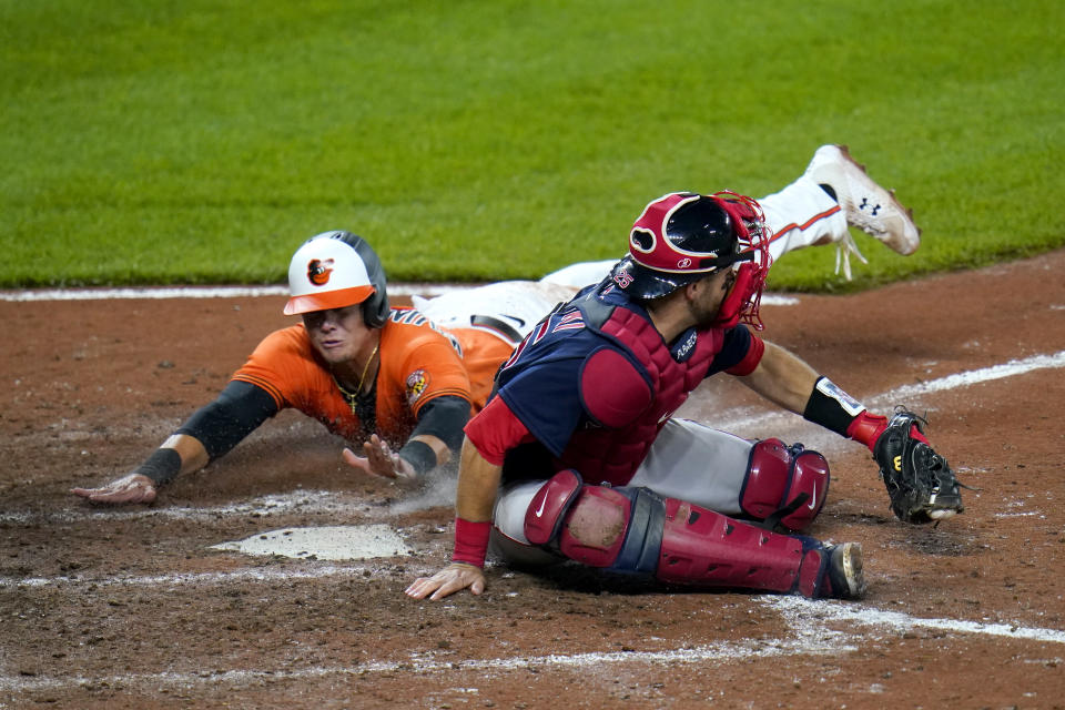 Baltimore Orioles' Ryan Mountcastle, left, slides in ahead of the tag by Boston Red Sox catcher Kevin Plawecki on a fielders choice ground ball by Orioles' Maikel Franco during the eighth inning of a baseball game, Saturday, April 10, 2021, in Baltimore. The Red Sox won 6-4 in ten innings. (AP Photo/Julio Cortez)
