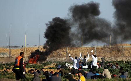 Palestinian medics raise up their hands as they try to evacuate a wounded demonstrator during protest at the Israel-Gaza border fence, in the southern Gaza Strip