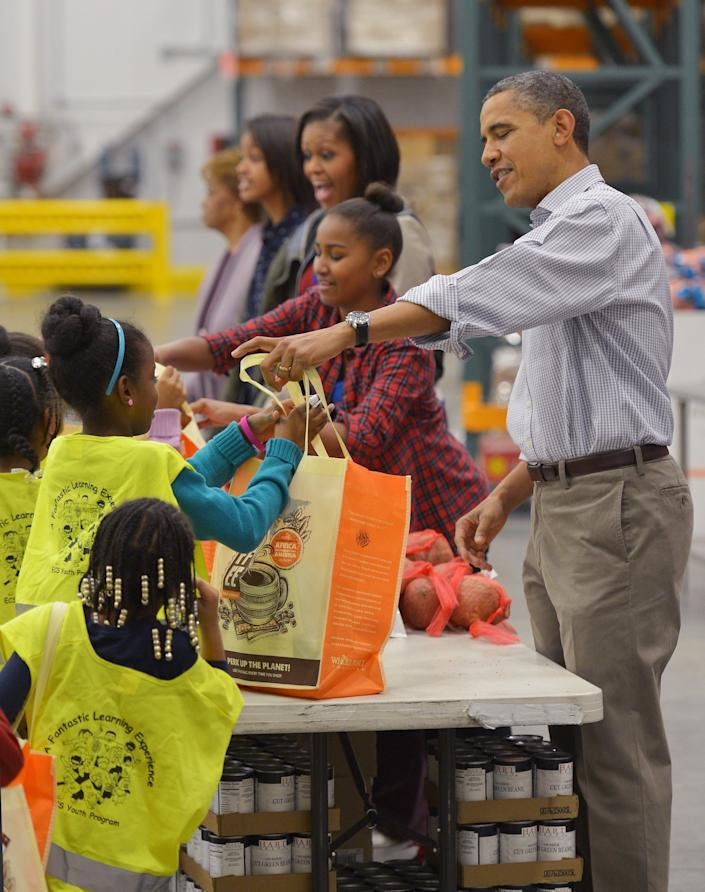 The Obamas distributed food at the Capitol Area Food Bank in Washington, DC, in 2012. (Photo: MANDEL NGAN via Getty Images)