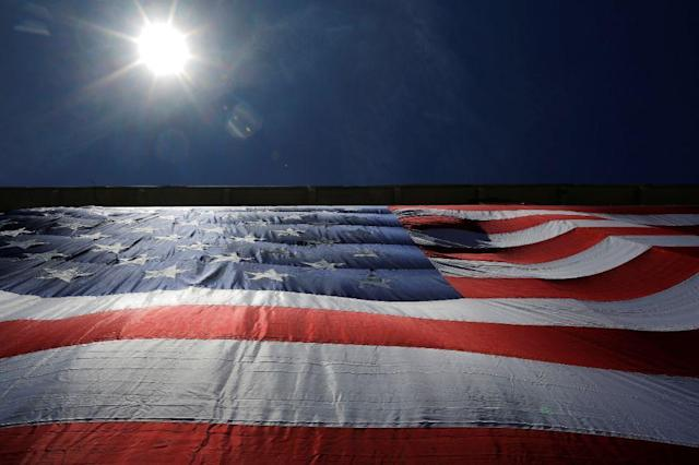 As 95-by-50-foot American flag is unfurled on the side of an apartment complex, a replica of the