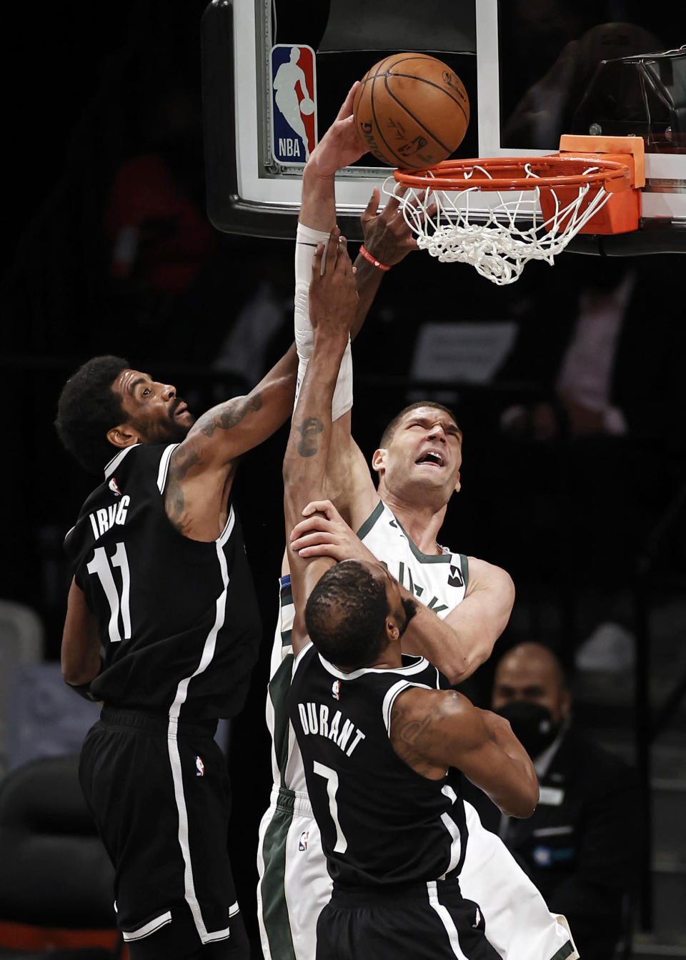 Milwaukee Bucks center Brook Lopez dunks between Brooklyn Nets' Kevin Durant (7) and Kyrie Irving (11) during the second half of Game 1 of an NBA basketball second-round playoff series Saturday, June 5, 2021, in New York. (AP Photo/Adam Hunger)