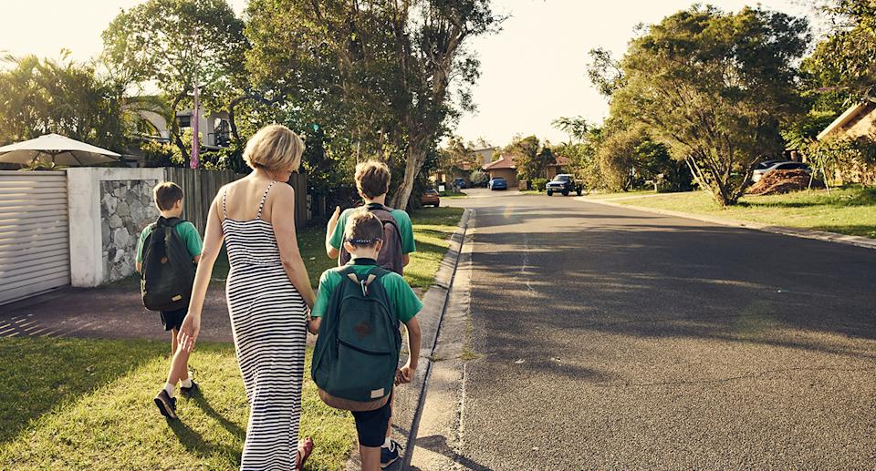 A group of children and a woman walk along a suburban road. Source: Getty Images