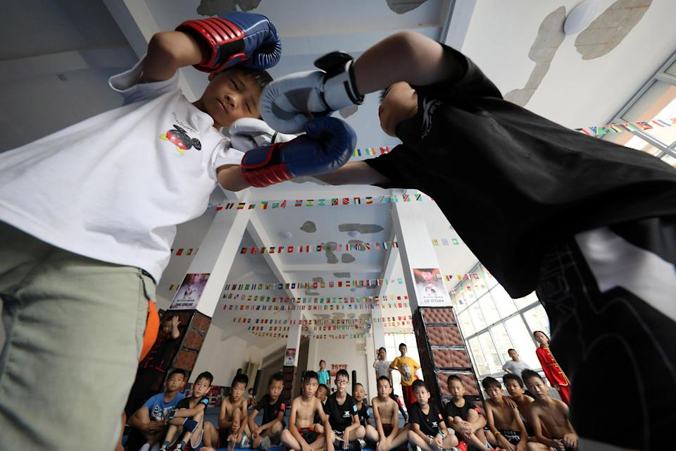Image: Young students practice Sanda fighting skills in the gymnasium. Danzhai County, Guizhou Province, China (Costfoto / Barcroft Media via Getty Images file)