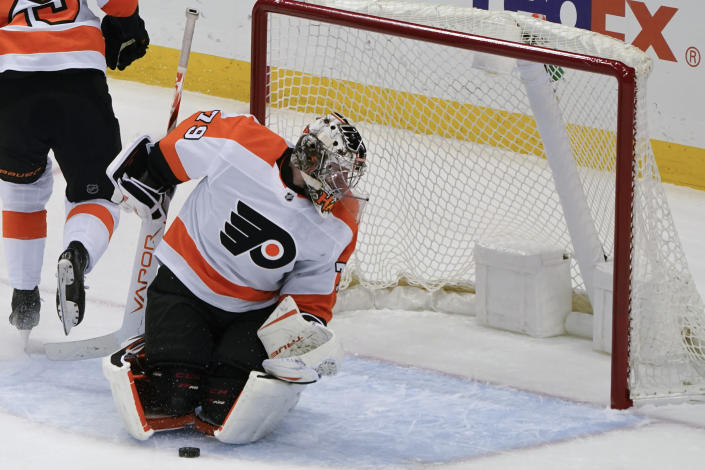 Philadelphia Flyers goaltender Carter Hart looks behind him as the puck is in front of him during the first period of an NHL hockey game against the Pittsburgh Penguins, Tuesday, March 2, 2021, in Pittsburgh. (AP Photo/Keith Srakocic)
