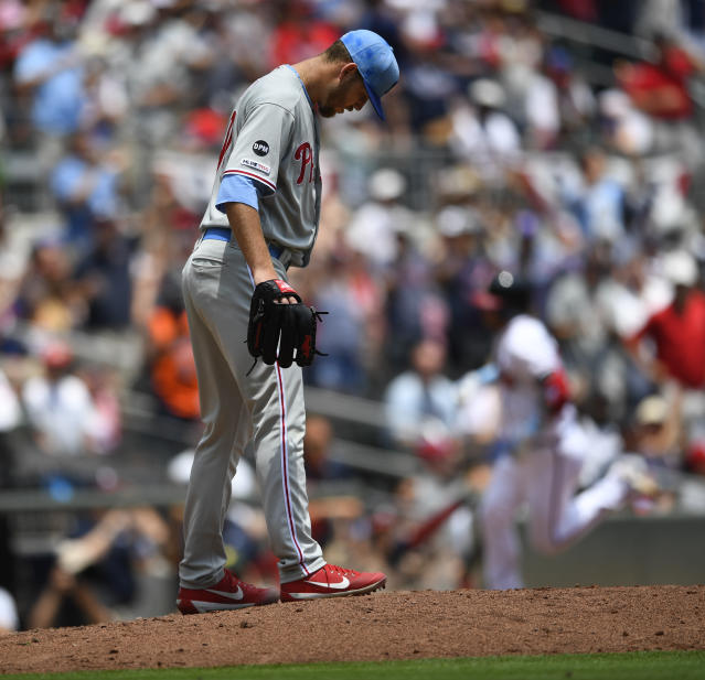 Philadelphia Phillies pitcher Cole Irvin, foreground, smoothes the mound as Atlanta Braves' Josh Donaldson, back right, runs bases after hitting a two-run home run in the third inning of a baseball game Sunday, June 16, 2019, in Atlanta. (AP Photo/John Amis)