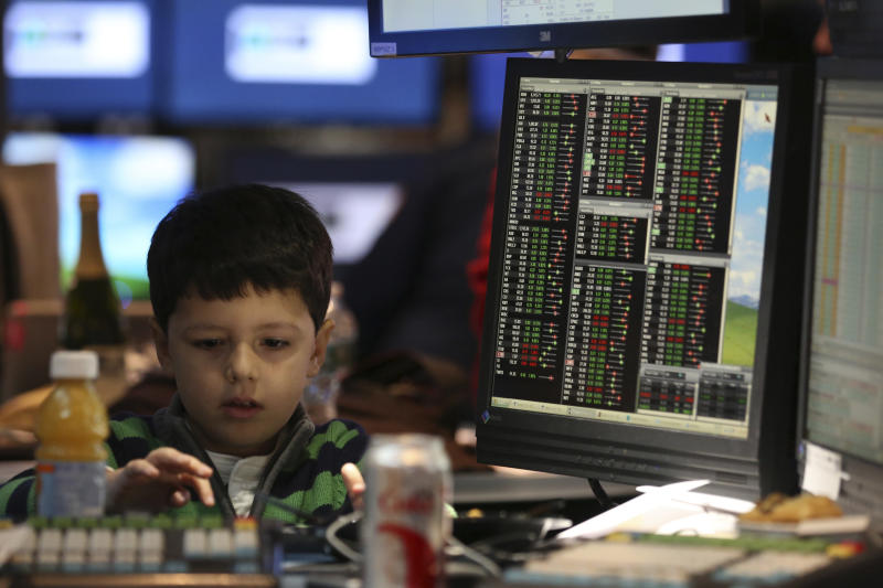 A young boy works at a post on the floor of the New York Stock Exchange November 29, 2013. Traders traditionally bring their kids to work for the half day of trading on the Friday after the Thanksgiving holiday. REUTERS/Brendan McDermid (UNITED STATES - Tags: BUSINESS)
