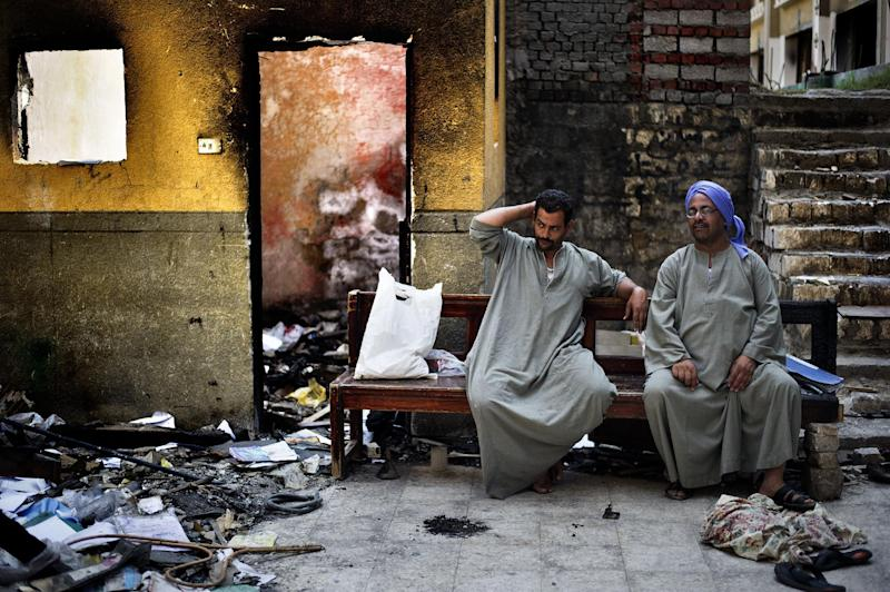 Egyptian Coptic Christians sit on a bench near debris that remain in the courtyard of Amba Moussa Coptic church after it was vandalized and torched by unknown assailants earlier this month on August 27, 2013 in the central Egyptian city of Minya (AFP Photo/Gianluigi Guercia)