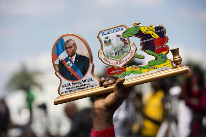A supporter of Haiti's new President Jovenel Moise holds up his image with Haiti's map and the National Palace, before the earthquake, during his inauguration ceremony in Port-au-Prince, Haiti, Tuesday Feb. 7, 2017. Moise was sworn as president for the next five years after a bruising two-year election cycle, inheriting a struggling economy and a deeply divided society. (AP Photo/Dieu Nalio Chery)