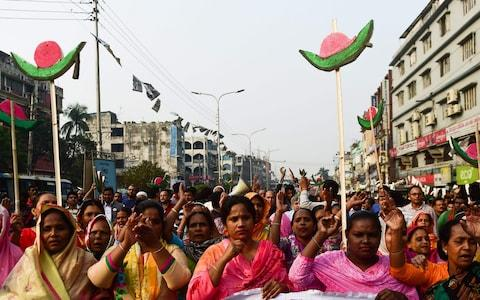 Supporters of Bangladesh Awami League march along a street as they take part in a rally ahead of December 30 general election vote - Credit: MUNIR UZ ZAMAN/AFP