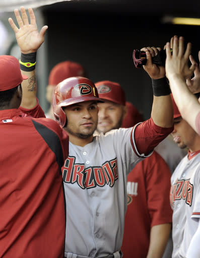 Arizona Diamondbacks Gerardo Parra is congratulated by his teammates after scoring in the first inning of a baseball game against the Colorado Rockies on Thursday, June 5, 2014, in Denver. (AP Photo/Chris Schneider)