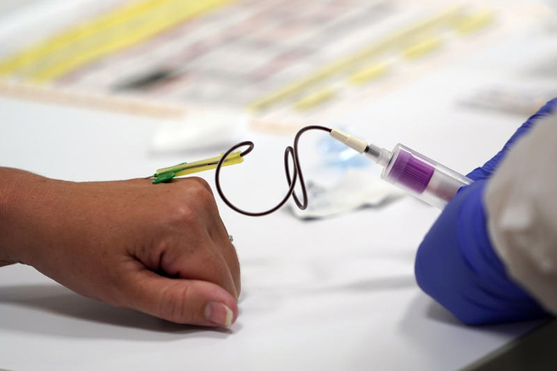 A Phlebotomist draws blood from a patient for COVID-19 antibody testing at Principle Health Systems and SynerGene Laboratory Tuesday, April 28, 2020, in Houston. The company, which opened two new testing sites Tuesday, is now offering a new COVID-19 antibody test developed by Abbott Laboratories. (AP Photo/David J. Phillip)