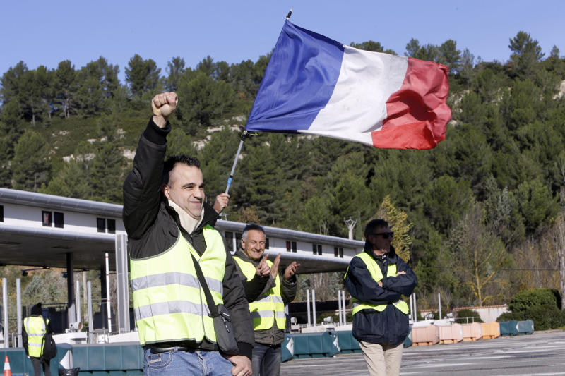 A demonstrators wearing a yellow vest clenches his fist as protesters open the toll gates on a motorway near Aix-en-Provence, southeastern France, Tuesday, Dec. 4, 2018. French Prime Minister Edouard Philippe announced a suspension of fuel tax hikes Tuesday, a major U-turn in an effort to appease a protest movement that has radicalized and plunged Paris into chaos last weekend. (AP Photo/Claude Paris)