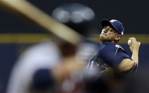 Milwaukee Brewers starting pitcher Marco Estrada throws to Atlanta Braves' Martin Prado, left, during the first inning of a baseball game, Tuesday, Sept. 11, 2012, in Milwaukee. (AP Photo/Morry Gash)